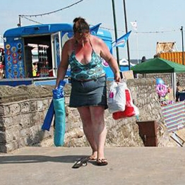 Fat , sunburned woman with cigarette and flip flops at the seaside