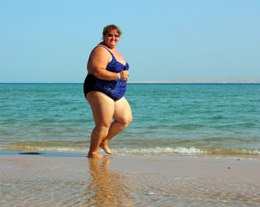 overweight woman running on beach