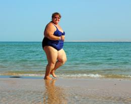 overweight woman running on beach