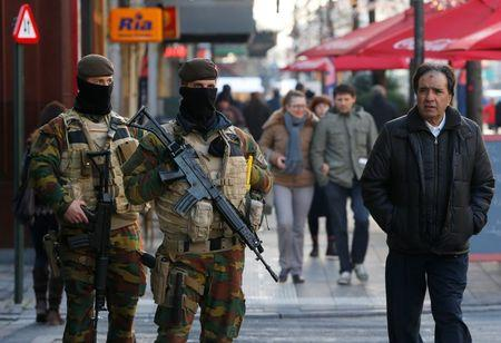 Belgian soldiers patrol in central Brussels as police searched the area during a continued high level of security following the recent deadly Paris attacks