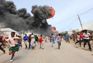 People escape from the direction of a huge fire-ball after an accidental explosion at a petrol storage facility within the former United States residential housing in capital Mogadishu September 3, 2013. REUTERS/Feisal Omar (SOMALIA - Tags: DISASTER ENERGY)